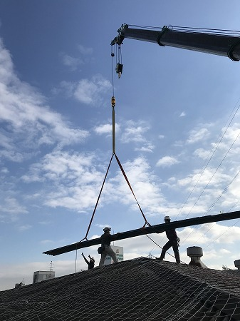 屋根の上で数人が鋼板屋根材を置いて行きます。