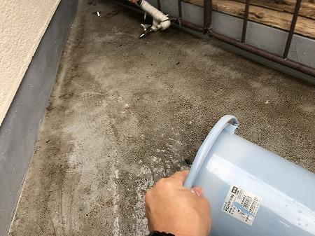 バケツでベランダに貯まった水をかき出します。
