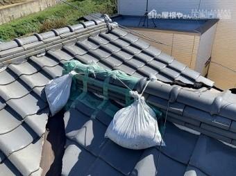 棟止まり部分のノシ瓦が崩れたのか、養生テープと土嚢で固定されています。